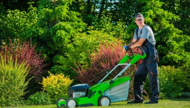 Smiling Professional Gardener with His Gasoline Lawn Mower. Professional Summer Landscaping Works